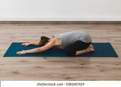 Young woman doing yoga in child's pose
