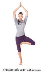 Young woman doing yoga exercise tree-pose isolated on white background