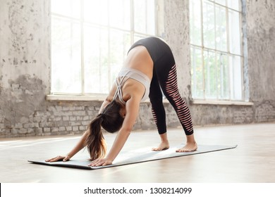 Young woman doing yoga exercise at home on mat in downward-facing dog pose stretching back