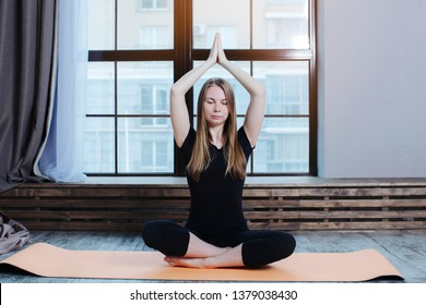 young woman doing yoga exercise sukhasana, hands namaste overhead  on yoga mat and relax breathing at studio.