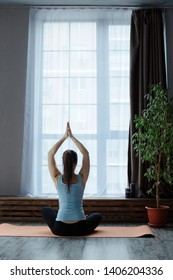 young woman doing yoga exercise sukhasana, hands namaste overhead  facing the large window to the floor on yoga mat and meditation and relax breathing at studio. back view