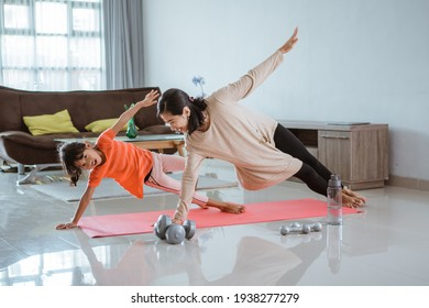 Young woman doing yoga exercise at at home with her daughter together