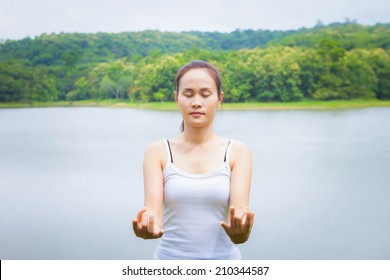 Young woman doing yoga exercise in green park