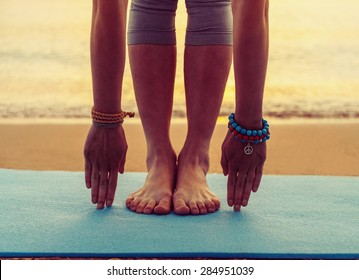 Young woman doing yoga exercise on beach near the sea at sunset in summer, face is not visible