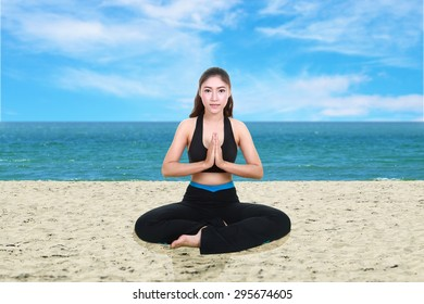 Young woman doing yoga exercise on the beach
