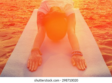Young woman doing yoga exercise on beach at sunset in summer, woman stretching her back. Image with sunlight effect