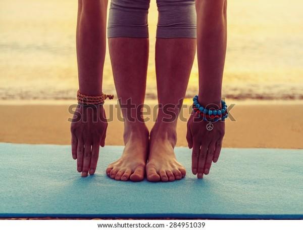 Junge Frau Yoga-Bewegung am Strand bei Sonnenuntergang im Sommer, Gesicht nicht sichtbar ist