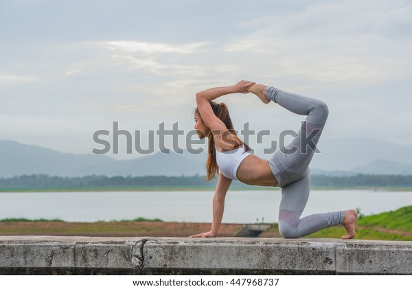 Young woman doing Yoga exercise in beautiful mountain lakes background