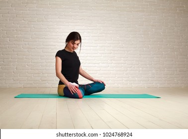 Young woman doing yoga exercises sitting in lotus pose