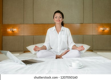 Young woman doing yoga exercises on the bed with laptop and coffee at home