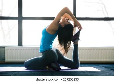 Young woman doing yoga exercises on yoga mat at gym