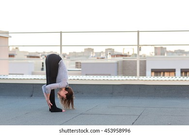 Young woman doing yoga and doing exercises on the mat on the roof.