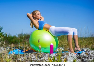 Young woman doing yoga exercises on the ball