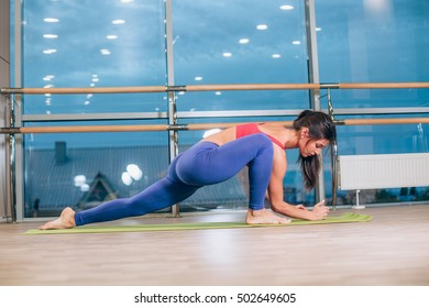 Young woman doing yoga exercises on mat at gym