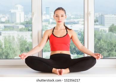 Young woman doing yoga meditation. indoor studio portrait inside room interior