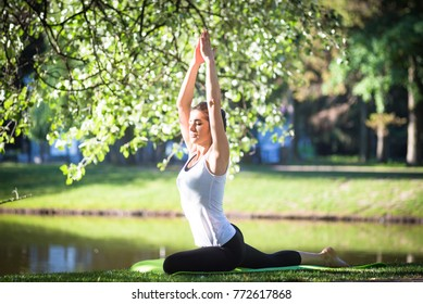 Young woman doing yoga in morning park near lake. Workout at the street