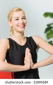 Young woman doing yoga moves, or meditating at home