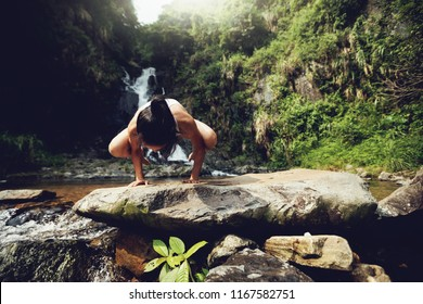 Young woman doing yoga near waterfall in tropical forest