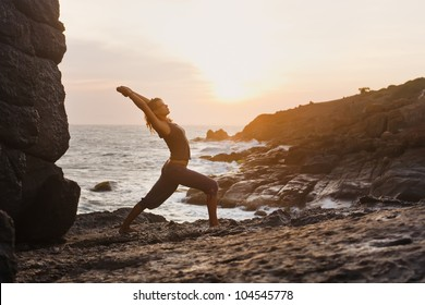 Young woman doing yoga on a rocky seashore. Doing warrior position