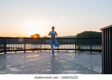 Young woman is doing yoga on the sunrise. Beautiful girl is practicing yoga standing in Vrikshasana pose on the morning