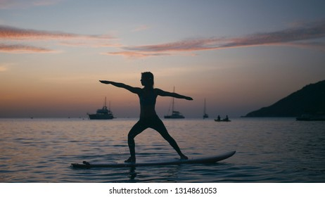 Young woman doing yoga on sup board with paddle at sunset. Concept of harmony with the nature, free and healthy living, freelance, remote business.