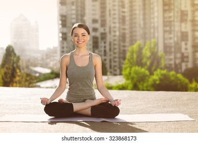 Young woman doing yoga on the mat on the roof, sitting in lotus posture, looking at camera and smiling