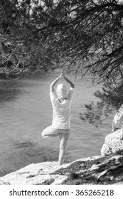 young woman doing yoga on the rocks next to the sea