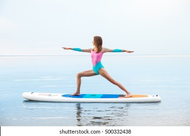 Young woman doing yoga on sup board with paddle. Meditative pose, side view - concept of harmony with the nature, free and healthy living, freelance, remote business.