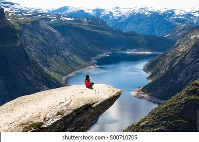 Young woman doing yoga on Trolltunga. Happy girl enjoy beautiful lake and good weather in Norway.