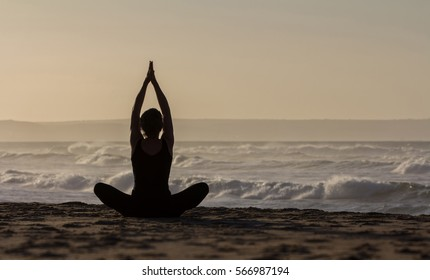 young woman doing yoga on the beach at sunrise sunset at peace with her body and the world
