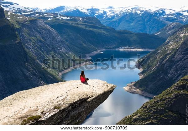 Young woman doing yoga on Trolltunga. Happy girl enjoy beautiful lake and good weather in Norway.