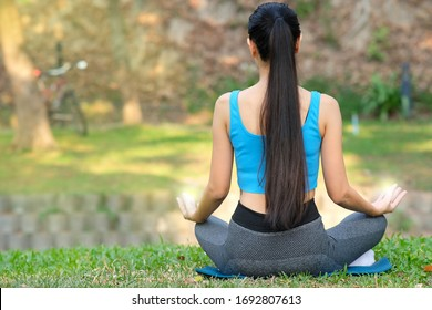 young woman doing yoga in the park and yoga relaxing in nature concept