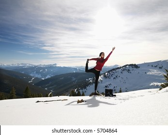Young woman doing yoga pose on rock in snow in mountainous terrain.