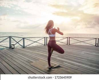 Young woman doing yoga at sunrise, hands together in prayer position namaste. People exercising and practicing mindfulness and mediation outdoors