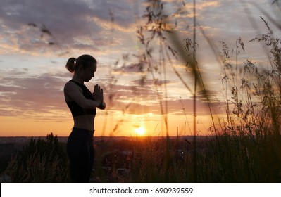 Young woman doing yoga in sunrise