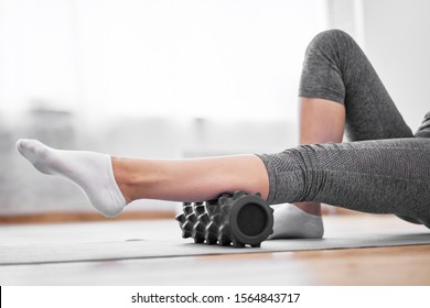 Young woman doing yoga while lying on massager on rug on wooden floor against background of window in gym