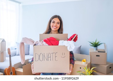 Young woman with donation box at home. Donation box for poor with clothing in female hands. Woman donates clothing to shelter. Cheerful woman holds box of donated clothing