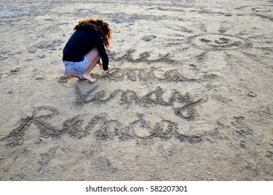 young woman drawing into a sand on the beach