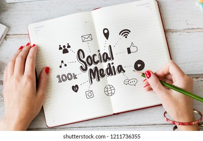 Young woman drawing social media in a notebook
