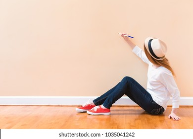 Young woman drawing something on a big open wall