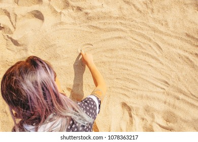 Young woman draws on the sand with her finger, top view.