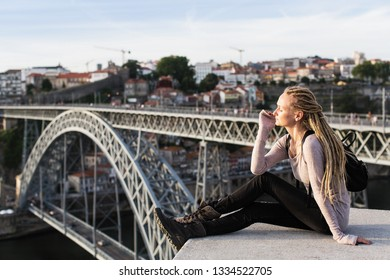 Young woman with dreadlocks sitting near bridge of Dom Luis I, Porto, Portugal.