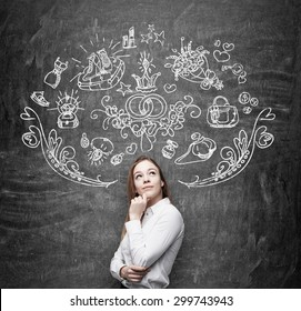 Young woman is dreaming about sopping. Shopping icons are drawn on the black chalkboard.