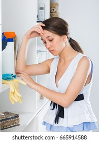 Young woman is dreaming while cleaning home.