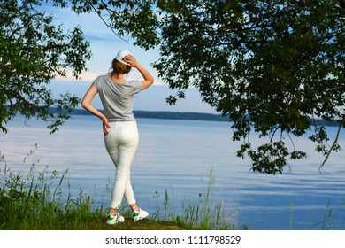 Young woman in dress and hat sits on lake shore under large tree and looks at sunset on horizon on warm summer evening. quiet scene of dreaming girl in nature. Attractive girl relaxes on outdoor