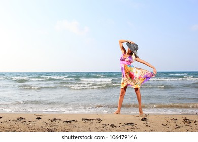 Young woman in dress and hat walking on beach