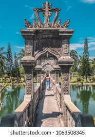 Young woman in dress on bridge in Water Palace Soekasada Taman Ujung on Bali Island in Indonesia. Amazing old architecture. Travel and holidays background. Vertical image.