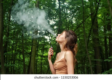 young woman in dress smoking an electronic cigarette in the forest, smells good