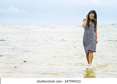 Young woman in dress walking in the sea
