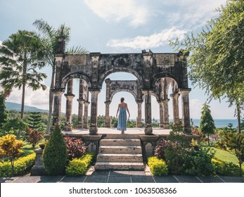 Young woman in dress in Water Palace Soekasada Taman Ujung Ruins on Bali Island in Indonesia. Amazing old architecture. Travel and holidays background.